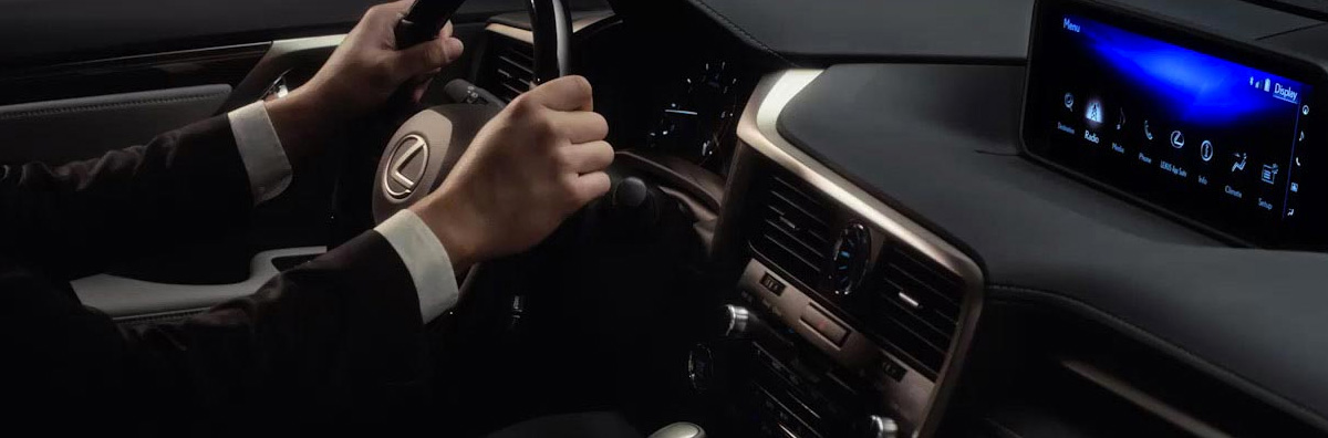 Man in a suit with his hands on the wheel of a Lexus