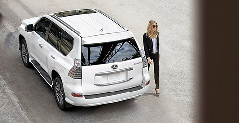 Upper rear view of Lexus GX with lady walking beside it