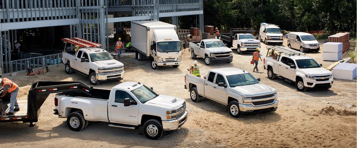 LINEUP OF CHEVROLET COMMERCIAL VEHICLES ON A WORK SITE